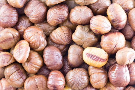 full frame: Full frame background texture of fresh whole roasted chestnuts for a healthy seasonal autumn snack or for use in cooking