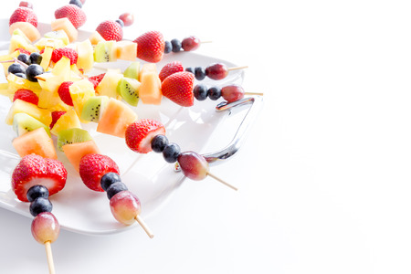 Serving of colorful healthy tropical fresh fruit kebabs with an assortment of exotic fruit on a white platter for a tasty vegan or vegetarian buffet, over white with copy space Stockfoto