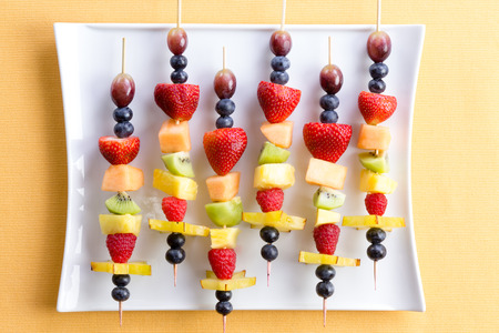 Healthy tropical summer fruit kebabs in a colorful arrangement on a modern white rectangular plate on a textured yellow table, overhead view
