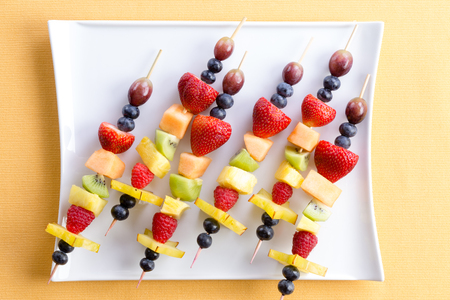 dessert plate: Fresh fruit shish kebabs arranged diagonally on a modern square plate for a healthy vegetarian buffet or dessert, viewed from above on a yellow summer table