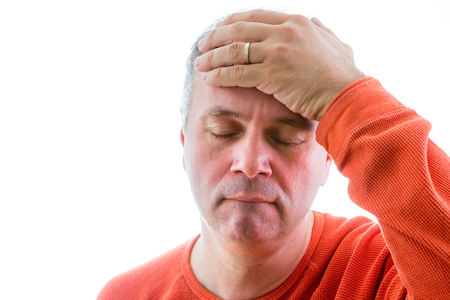 forgetful: Forgetful man holding his hand to his forehead with a painstaking expression as he struggles to remember something, head and shoulders on white
