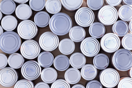 Background of multiple sealed food cans or tins viewed from overhead in an assortment of sizes filling the frame in a food and nutrition concept Stockfoto
