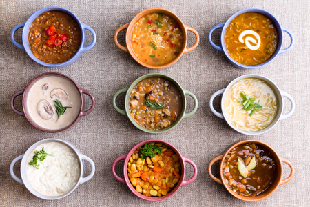 Assorted soups from worldwide cuisines displayed in bowls in three colorful lines garnished with cream and herbs in a World Of Soup concept, overhead view