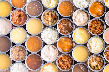Colorful background of neatly arranged rows of opened cans of assorted soup viewed full frame from above in a food abstract still life