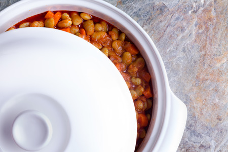 lima bean: Delicious savory lima bean casserole with carrots cooling off in a white ceramic casserole dish with the lid moved aside to view the contents, closeup overhead view on a stone counter