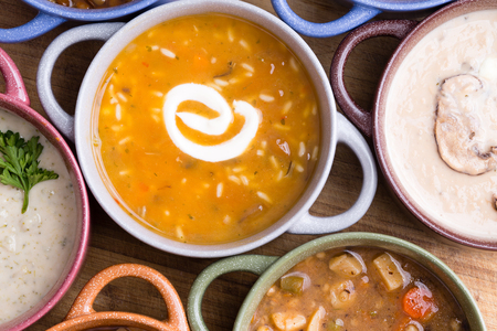 Overhead view of assorted soup in bowls with handles with focus to a cup of chicken broth with wild rice garnished with a twirl of sour cream