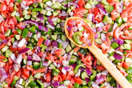 close up food: Colorful Turkish shepherd salad background food texture made from a variety of fresh finely diced vegetables with a wooden serving spoon viewed close up full frame from above