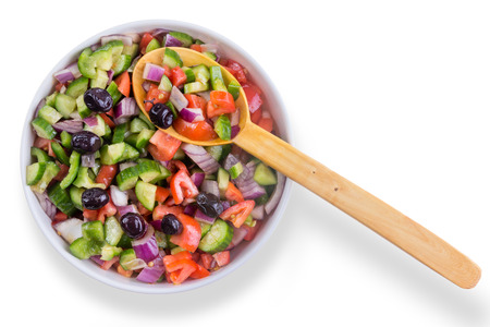 accompaniment: Fresh colorful Turkish shepherd salad with olives served in a round bowl with a wooden serving spoon as a healthy accompaniment to a meal, overhead on white Stock Photo