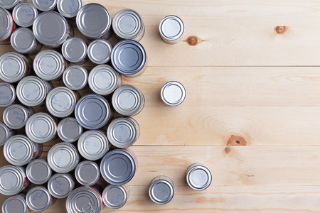 Conceptual background of multiple canned foods in sealed aluminum tins or cans of varying sizes arranged on a wooden table with copy space, overhead view