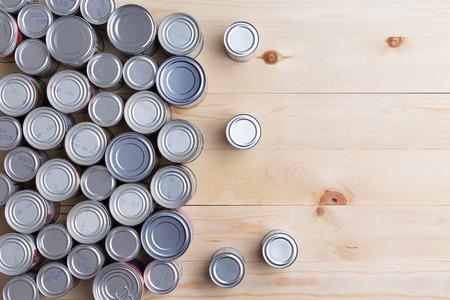 Fondo conceptual de múltiples alimentos enlatados en latas o botes de diferentes tamaños dispuestos sobre una mesa de madera con espacio de copia de aluminio cerradas, vista aérea