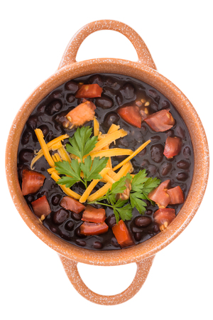 Bowl of nutritious black bean soup garnished with cheddar cheese, fresh parsley and tomato viewed close up from above isolated on white