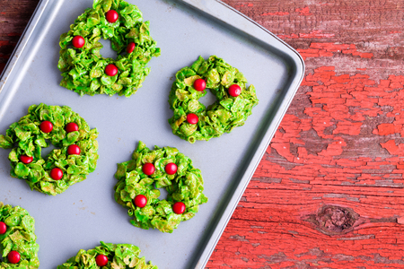 party tray: Freshly baked Christmas wreath cookies made with colorful green and red cornflakes and candy cooling on a metal baking tray on a red rustic table, overhead view with copy space