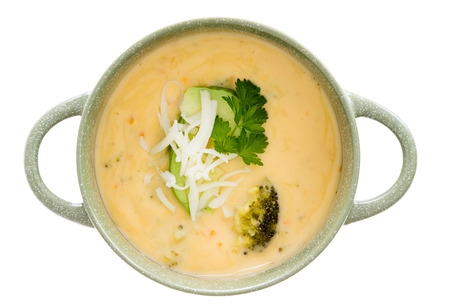 grates: Bowl of tasty cream of broccoli soup garnished with fresh parsley and grated cheddar cheese, overhead view isolated on white