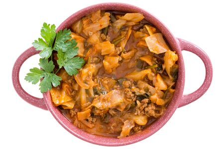 potherb: Nutritional cabbage soup with ground beef mince and seasoning garnished with fresh parsley served in a pink bowl for an appetizing winter meal, overhead on white
