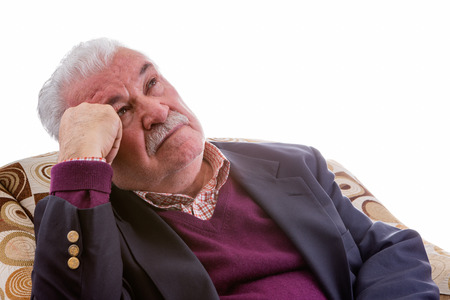 perturbed: Elderly retired man relaxing in a comfortable armchair staring thoughtfully up into the air with an intent expression, isolated on white with copy space