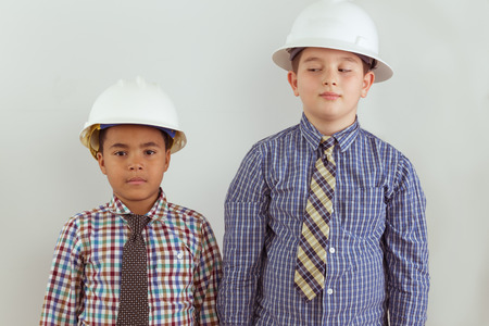 anticipate: Two multiracial young aspiring tween engineers dressed in ties and hardhats standing side by side against a wall as the two friends anticipate their future careers
