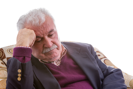 downcast: Tired elderly retired gentleman sitting thinking in a comfortable armchair resting his head on his hand with his eyes downcast, close up isolated on white
