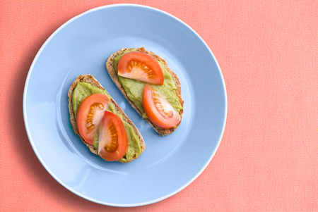 Top view of blue plate with healthy avocado and tomato sandwich over pink cloth background