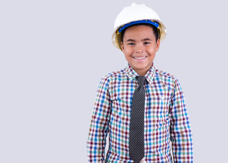 Smiling little boy wearing white hard hat and necktie with checkered shirt on gray background