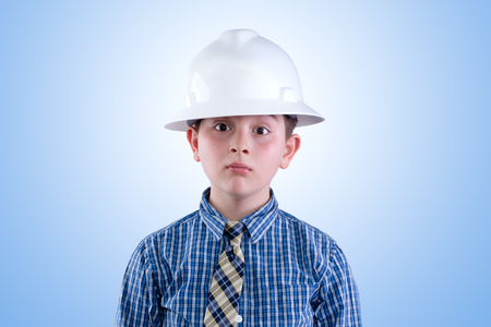 tween boy: Aspiring young tween boy dreaming of becoming an engineer in hardhat and necktie with a whimsical expression - I am going to be an engineer - against a blue background Stock Photo