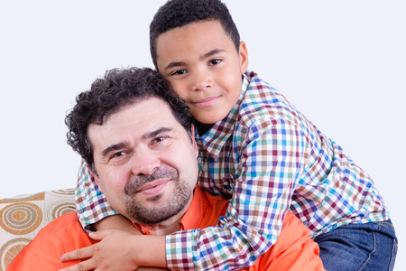 Cheerful child in checkered shirt with grin hugging his smiling father with beard from behind