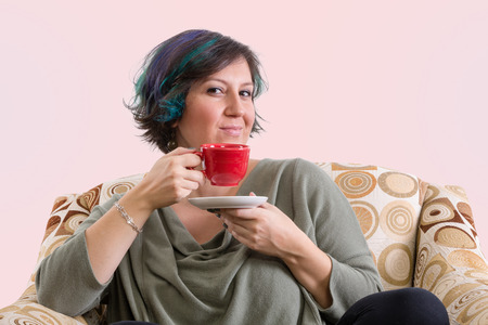 appraising: Single intelligent grinning adult female holding red coffee mug while sitting in a comfortable sofa chair Stock Photo