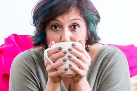 Excited woman with wide eyes and painted fingernails holding coffee mug partially covering her face Фото со стока