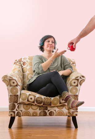 Dissatisfied woman sitting alone on sofa chair is given red coffee mug by an unidentified man
