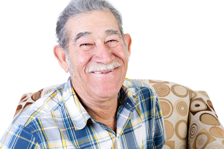 Handsome single Mexican man sitting on chair with big smile and mustache in flannel shirt