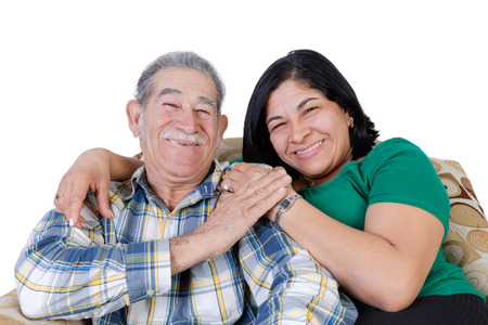 Happy Mexican senior with mustache touching hand of happy daughter sitting together on sofa
