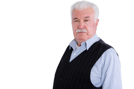 sombre: Firm and angry senior man wearing vest with intimidating and serious expression over isolated background