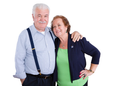 Married senior husband and wife standing together in harmony looking at camera over white background