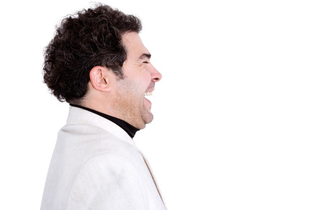 high spirited: Isolated sideways view of attractive, middle-aged male with curly hair and white jacket laughing