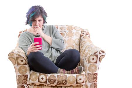 persona leyendo: Individual de mediana edad mujer regordeta con expresión preocupada mirando teléfono en el sofá cómodo Foto de archivo