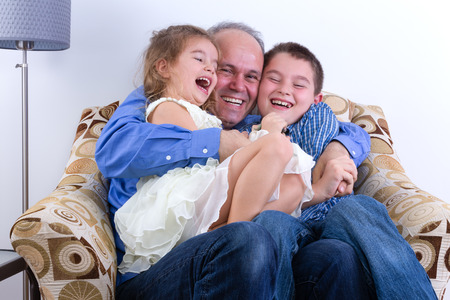 hilarity: Middle-aged father with two laughing young kids, a girl and boy, on his lap sitting in an armchair enjoying a moment of fun and hilarity as a family Stock Photo