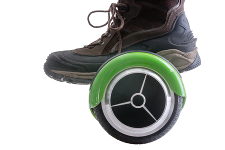 board: Big boot riding a modern motorised green hover board or self balancing scooter, the new trendy mode of transportation, isolated on white