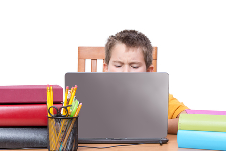 Top of head for single male child studying while surrounded with large books in front of laptop over white background Imagens - 52581496