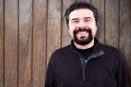 goatee: Half Body Shot of a Middle Aged Man with Goatee Beard, Sincerely Smiling at the Camera, Against Wooden Wall with Copy Space.