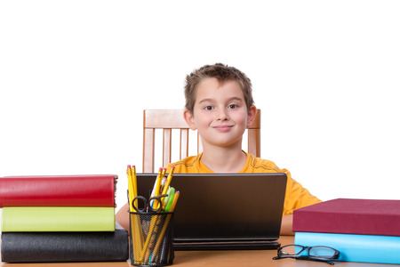 classwork: Smiling little boy at desk with laptop in between piles of large books and cup of pencils and pens