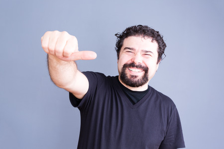 high spirited: Waist Up Portrait of Joyful Laughing Man with Beard and Curly Hair Giving Side Thumb Hand Gesture Towards Camera in Studio with Gray Background and Copyspace Stock Photo