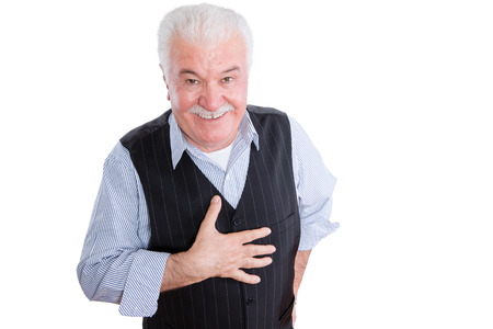 obliged: Isolated single mature man with smile and respectful expression gesturing as hand is on chest