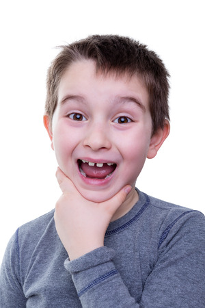 dismayed: Cute little boy in gray shirt holding his chin with wide open mouth and big smile over white background