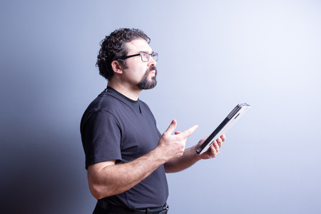 side lighting: Profile of Man Wearing T-Shirt and Eyeglasses Deep in Thought While Holding Computer Tablet in Studio with Gray Background, Side Lighting and Copy Space Stock Photo