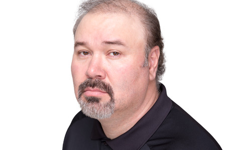 aged: Close up of downcast middle aged male in black shirt with graying beard and mustache over white background Stock Photo