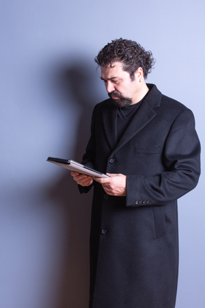 three quarter length: Three Quarter Length of Man with Beard and Curly Hair Wearing Long Dark Trench Coat and Looking Down Seriously at Computer Tablet in Studio with Gray Background and Copy Space