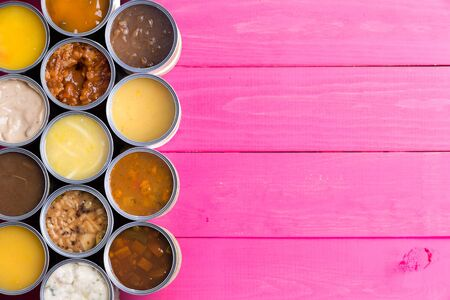canned meat: High Angle View of Open Cans of Soup in Wide Variety of Flavors on Bright Pink Painted Wooden Background with Ample Copy Space