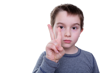 non verbal: Close up of serious little boy gesturing with two fingers as if to count or display a sign language letter Stock Photo
