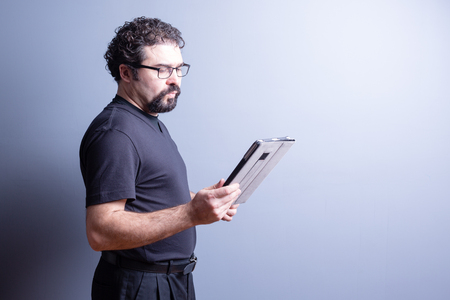 side lighting: Profile of Man Wearing T-Shirt and Eyeglasses Looking Serious and Reading from Computer Tablet in Studio with Gray Background, Side Lighting and Copy Space