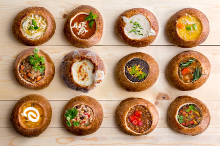 bread: High Angle View of Various Comforting and Savory Gourmet Soups Served in Hollowed Out Bread Bowls on Wooden Table Surface