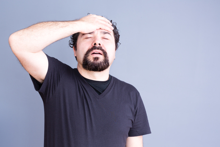 regretful: Waist Up of Frustrated Regretful Man with Beard Wearing Dark T-Shirt Holding Head and Hand on Forehead in Studio with Gray Background and Copy Space Stock Photo